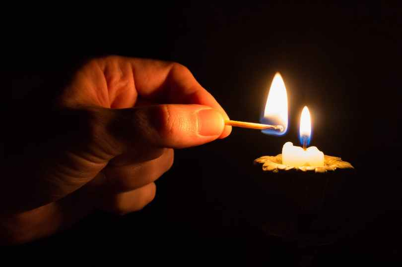 person holding match stick with fire in front of candle with fire